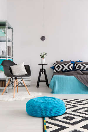 Shot of a minimalist bedroom with a blue knitted pouffe in the middle and a bed decorated with cushions in the back Stock Photo