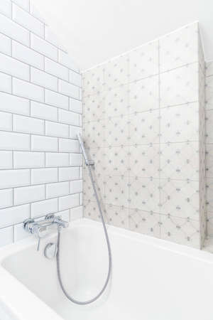 chromium plated: White corner of a minimalist bathroom with brick-resembling tiles and a ceramic bathtub