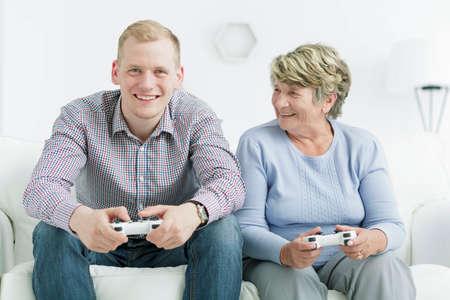 jugando videojuegos: Disparo de un hombre joven feliz jugando juegos de video con su abuela