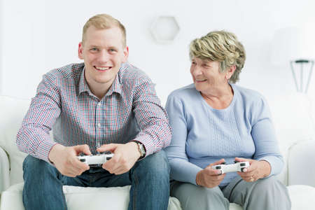 playing video games: Shot of a happy young man playing video games with his grandma