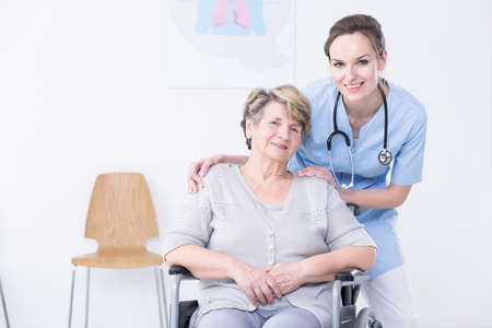 Young, smiled doctor standing behind the elder woman with hands on seniors shoulder
