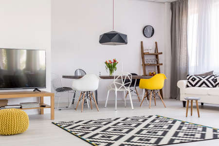 panelled: Very spacious dining and living room in a modern apartment, with black and white accessories and a large carpet