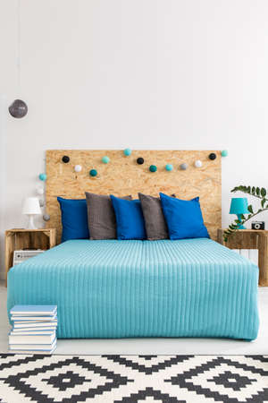 nightstands: Shot of a large bed in a light interior with DIY ideas for nightstands and bed backboard