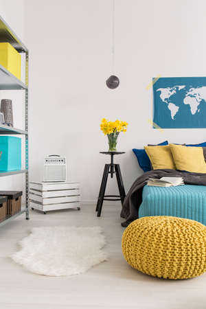 pouffe: Bedroom corner with metal rack, wooden box nightstand with amplifier on it, and a large bed