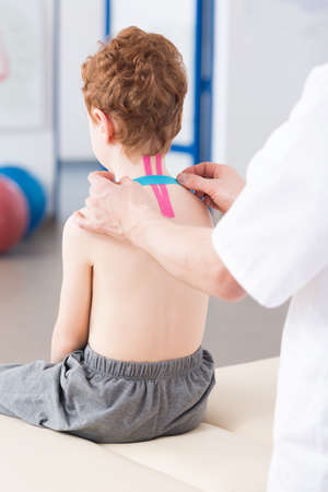 posture correction: Physiotherapist applying kinesio tape on childs neck