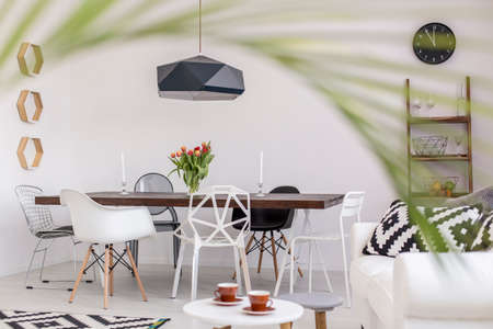 wood panelled: Modern dining room with a stylish table and designer chairs seen from the perspective of a blurred palm tree leaf Stock Photo