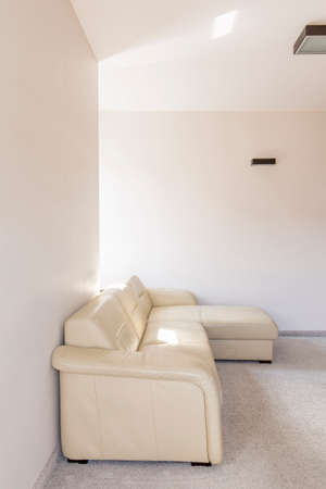 comfort room: Corner of a white room with a leather sofa and fitted carpet