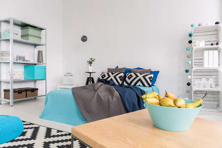 roomy: Roomy bedroom in a modern flat, with wooden coffee table in the first ground and a cosy bed with blankets behind