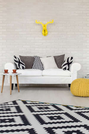 Stylish and comfortable sofa in a modern interior with white brick wall, decorative carpet and yellow cardboard antlers Stock Photo
