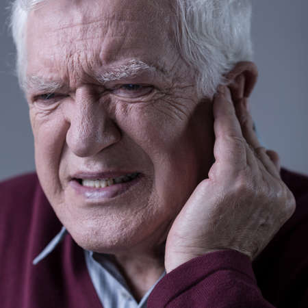 dolor de oido: hombre elegante mayor con el dolor de oído agudo
