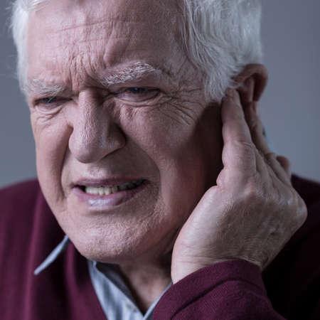 seniors suffering painful illness: Senior elegant man with sharp earache Stock Photo