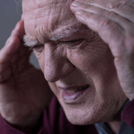 horrible: Close-up of older sad man with horrible headache Stock Photo