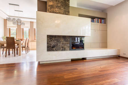 Rectangular marble fireplace in a spacious interior bordering illuminated dining room