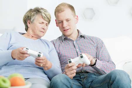 jugando videojuegos: Captura de una mujer mayor que juega videojuegos con su nieto