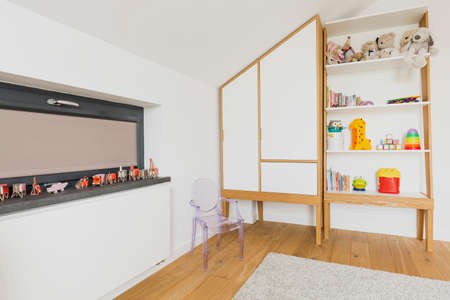 attic window: Corner of a childrens room in an attic, with horizontal window, fitted wardrobe and a transparent chair