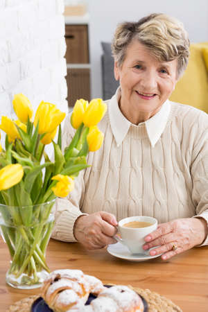Senior, smiled woman sitting at a wooden table with cup of coffee and with the vase of yellow tulips on