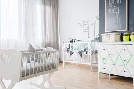 cradle: Baby room with baby cradle, white commode and wide window Stock Photo