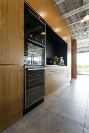 Very modern kitchen in post industrial style with wooden cabinet fronts, built in ovens and tiled floor Stock Photo