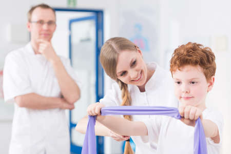 resistance: Ginger boy exercising with resistance band and two professional physiotherapist