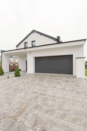 広大なコンクリート私道から見た車庫を持つ現代的な戸建住宅