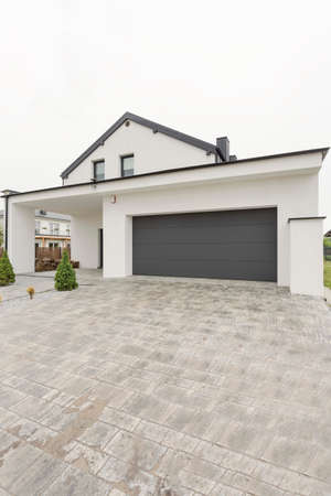 garage on house: Contemporary detached house with garage seen from a vast concrete driveway