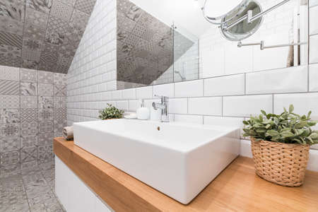 Contemporary bathroom corner with decorative tiles and a rectangular ceramic sink Stockfoto