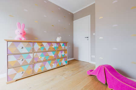 pouffe: Little girls room with a wonderful hand-decorated chest of drawers, white door and a pink pouffe in the shape of a wiener dog