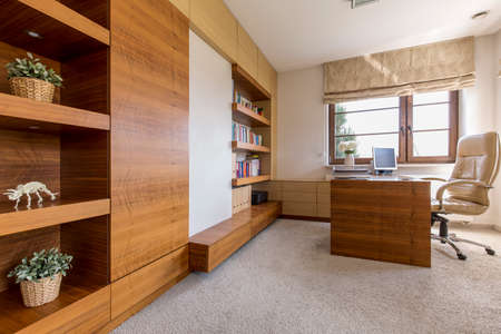 Bright office room in a house, with a leather swivel chair and a set of modern wooden furniture Archivio Fotografico