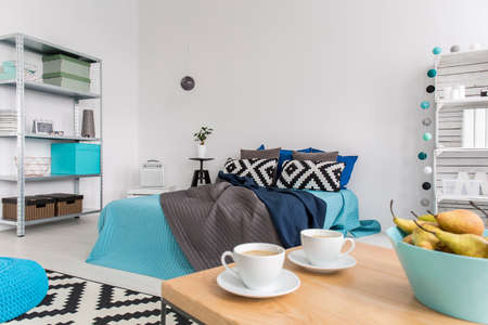 bedspread: Freshly renovated bedroom arranged in white and blue, with a wooden coffee table with coffee cups in the foreground