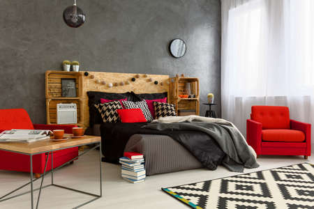 コンクリートの壁と現代的なベッドルームで赤い肘掛け椅子