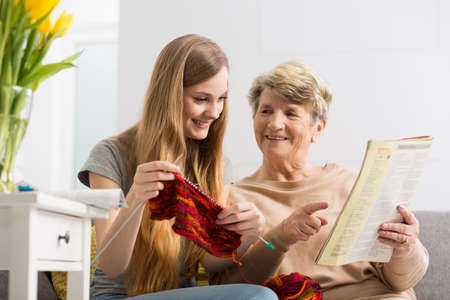 educator: Senior lady sitting on a couch with her granddaughter and teaching her needleworking with the instruction in her hand