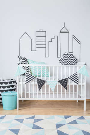amenities: Bright interior with baby cot and city theme on the wall