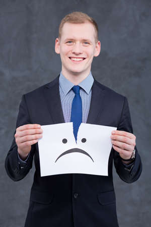 teared paper: Young, elegant man in suit holding a piece of teared paper with the sad mien and smiling Stock Photo