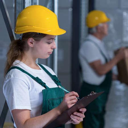 obrero: Trabajador femenino fabricaci�n celebraci�n de portapapeles y observando