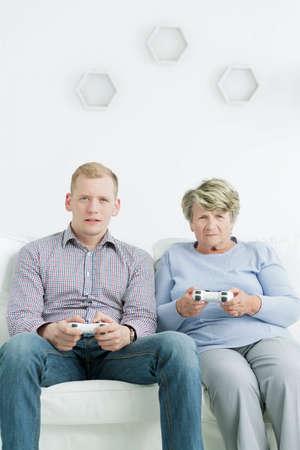 jugando videojuegos: Disparo de un nieto y su abuela jugando juegos de video