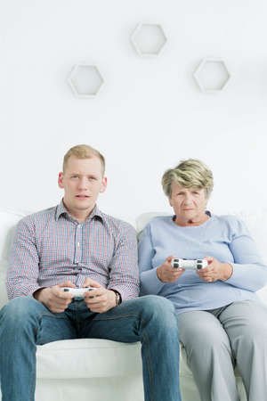 jugando videojuegos: Shot of a grandson and a grandmother playing video games together