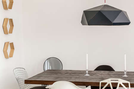 dining table and chairs: Close-up of a wooden table surrounded by avantgarde chairs in a minimalist dining room