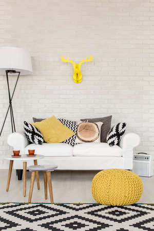 Stylish white sofa filled with pillows in a modern lounge room with white brick wall, decorative carpet and a lamp