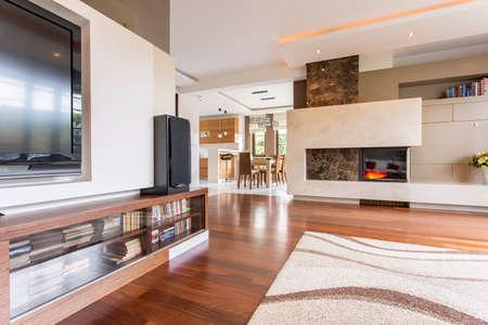 Spelonkachtige woonkamer met een tv-toestel en een marmeren open haard samen met een eetkamer in de achtergrond Stockfoto