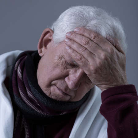 seniors suffering painful illness: Older sick man with high fever and headache Stock Photo