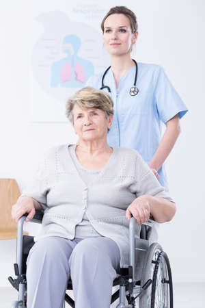 Smiled doctor standing behind the wheelchair with the elder woman Stock Photo