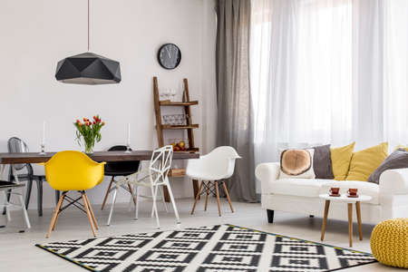 Spacious dining and living room in white and black with modern furniture and decorations