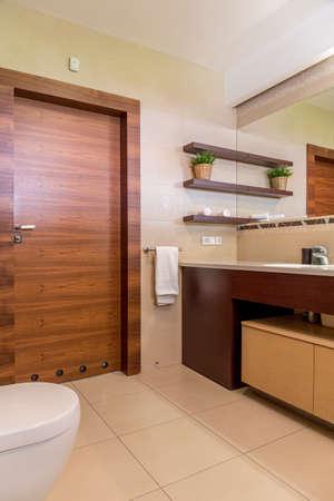 tiled floor: Contemporary bathroom in beige, with wooden door and tiled floor Stock Photo