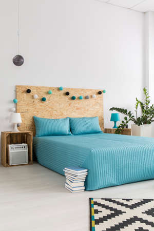 chipboard: Simple bed with light blue cover and cushions and a chipboard back, in a very light and simple interior Stock Photo