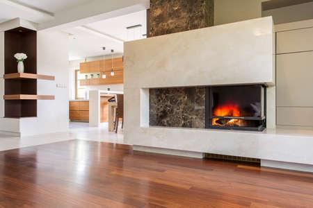 Marmeren open haard in een enorme woonkamer met panelen vloer, samen met lichte keuken