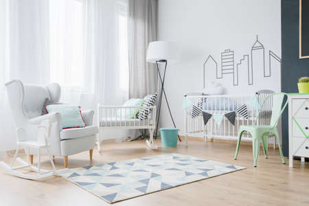 cosy: Peaceful area of baby room with cosy armchair and baby cradle