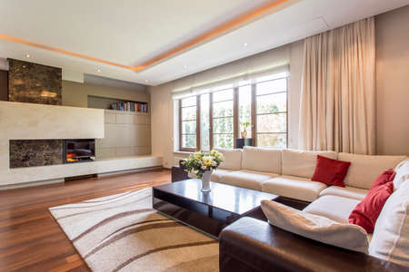 Luxurious living room in a villa, with a leather corner sofa and a fireplace