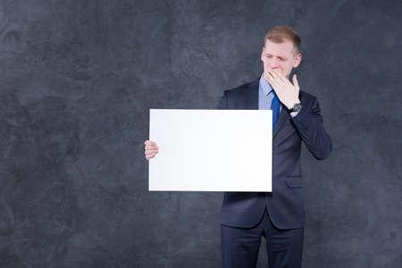 cansancio: hombre elegante joven y aburrido en juego, sosteniendo un pedazo de papel y cubriendo su boca con una mano Foto de archivo