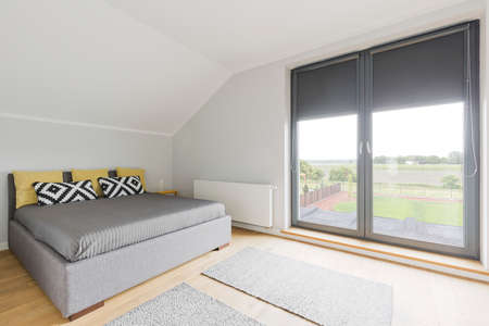 balcony window: Contemporary bedroom in a detached house outside the city, with a large balcony window overlooking the backyard and fields Stock Photo