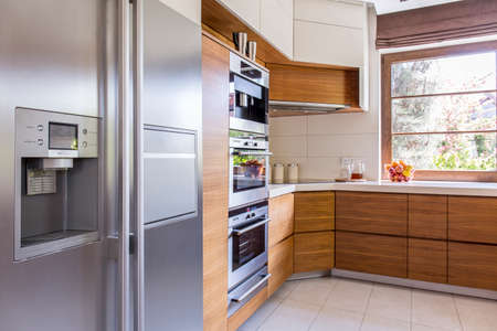 fronts: Corner of a freshly-renovated kitchen with wooden cabinet fronts and a side by side refrigerator Stock Photo